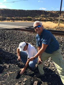 Chip Smith (right), Assistant for Environment, Tribal and Regulatory Affairs, Office of Assistant Secretary for Army Civil Works; and JR Inglis, Corps of Engineers Tribal Liaison, Portland District, dig down to find the depth of the coal debris along the tracks near Dallesport, WA. In some places, they found debris 4 to 6 inches deep.